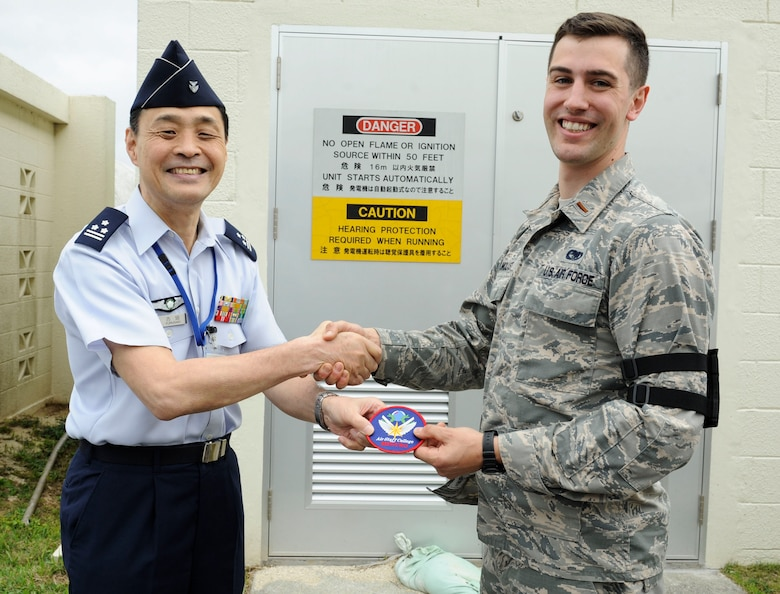 Japan Air Self-Defense Force Col. Riichi Furugaki, JASDF Air Staff College director of education department, presents a JASDF Air Staff College patch to U.S. Air Force 2nd Lt. William Holmquist, 18th Logistics Readiness Squadron fuels operations officer, April 27, 2017, at Kadena Air Base, Japan. The 18th LRS petroleum, oils and lubricants flight maintains relationships with fellow JASDF members by hosting frequent tours of their facilities. (U.S. Air Force photo by Senior Airman Lynette M. Rolen)