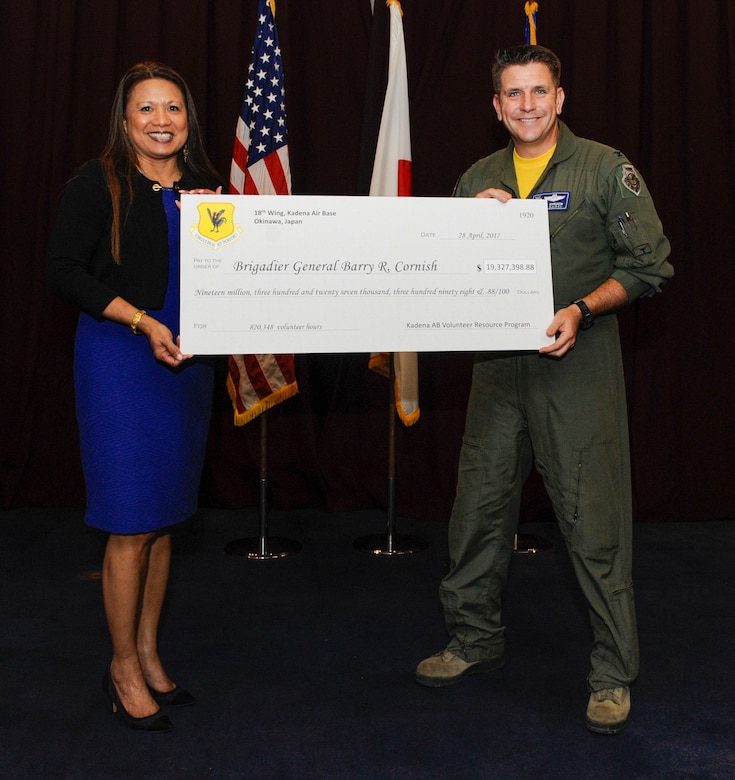 U.S. Air Force Col. Christopher Amrhein, 18th Wing vice commander, and Emiciosa Cox, 18th Force Support Squadron supervisory lead, hold a symbolic check from Kadena Volunteer Resource Program during the 18th Wing Annual Volunteer Recognition ceremony April 28, 2017, at Kadena Air Base, Japan. Team Kadena members contributed more than 820,000 volunteer hours to the base and local community over the past year. Thousands of volunteers from Kadena, including joint service members and civilians, saved the base more than $19 \million. (U.S. Air Force photo by Senior Airman Lynette M. Rolen)