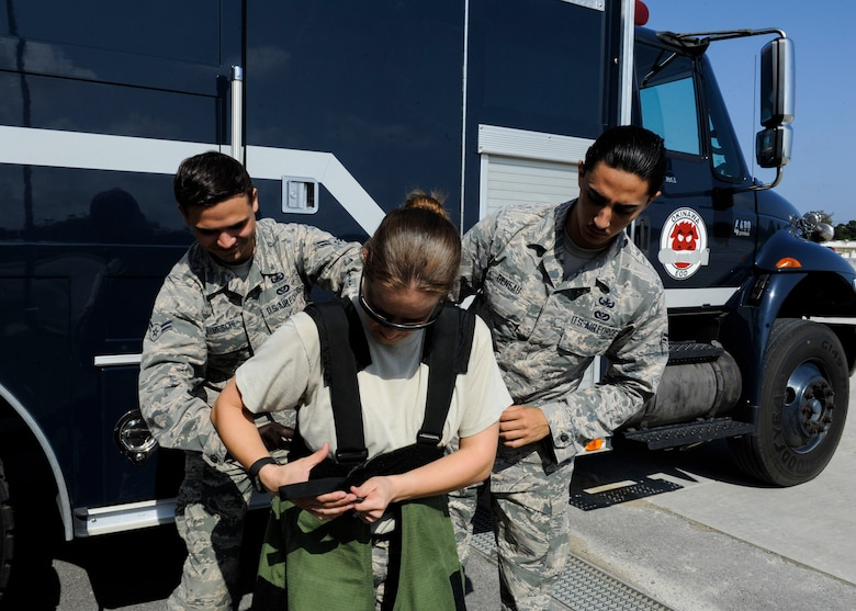 U.S. Air Force Airmen 1st Class Anthony Beschi and Quentin Deneau, 18th Civil Engineer Squadron Explosive Ordnance Disposal apprentices, assist Tech. Sgt. Rebecca Kimberling, 18th CES EOD supply NCO in charge, as she gets into an EOD bomb suit May 4, 2017, at Kadena Air Base, Japan. Explosive Ordnance Disposal response is made possible through team dynamics between NCOs and Airmen. (U.S. Air Force photo by Senior Airman Lynette M. Rolen)