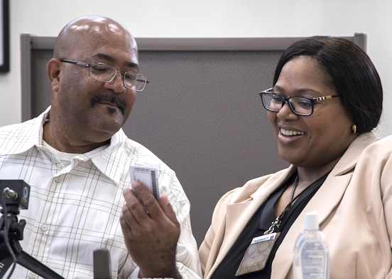 Michael L. Chavis, left, Gold Star parent, shows his new Gold Star Base Access ID card to Carla Diamond, right, U.S. Air Force Headquarters community readiness consultant, at Joint Base Andrews, Md., May 1, 2017. These cards are part of an Air Force initiative allowing Gold Star family members, immediate relatives of deceased Airmen, unescorted access to Air Force installations to visit buried loved ones, attend base events, and stop by Airmen and Family Readiness Centers for support. The Air Force initiative refers to parents, grandparents, siblings and adult children of Airmen killed in action, international terrorist attack against the U.S. or military operations while serving outside the U.S. as part of a peacekeeping force. (U.S. Air Force photo by Senior Airman Jordyn Fetter)