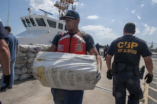 A crew member from Coast Guard Cutter Tarpon, an 87-foot Coast Patrol Boat homeported in St. Petersburg, Florida, and his crew offload 1,735 kilograms of cocaine, an estimated wholesale value of $56 million, Wednesday, May 3, 2017 at Coast Guard Sector St. Petersburg, Florida. The contraband was interdicted during four separate cases supporting Operation Martillo, a joint interagency and multi-national collaborative effort among 14 Western Hemisphere and European nations to stop the flow of illicit cargo by Transnational Criminal Organizations. (U.S. Coast Guard photo by Petty Officer 1st Class Michael De Nyse)