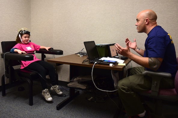 "Eva, a Buckley Youth, is interrogated by Special Agent Keith, 12th Field Investigations Squadron, during ""Bring Our Daughters and Sons to Work Day"" April 27, 2017, on Buckley Air Force Base, Colo. The interrogation method used replicated lie detector equipment and ""playful"" questions. (U.S. Air Force photo by Airman Jacob Deatherage/Released)"