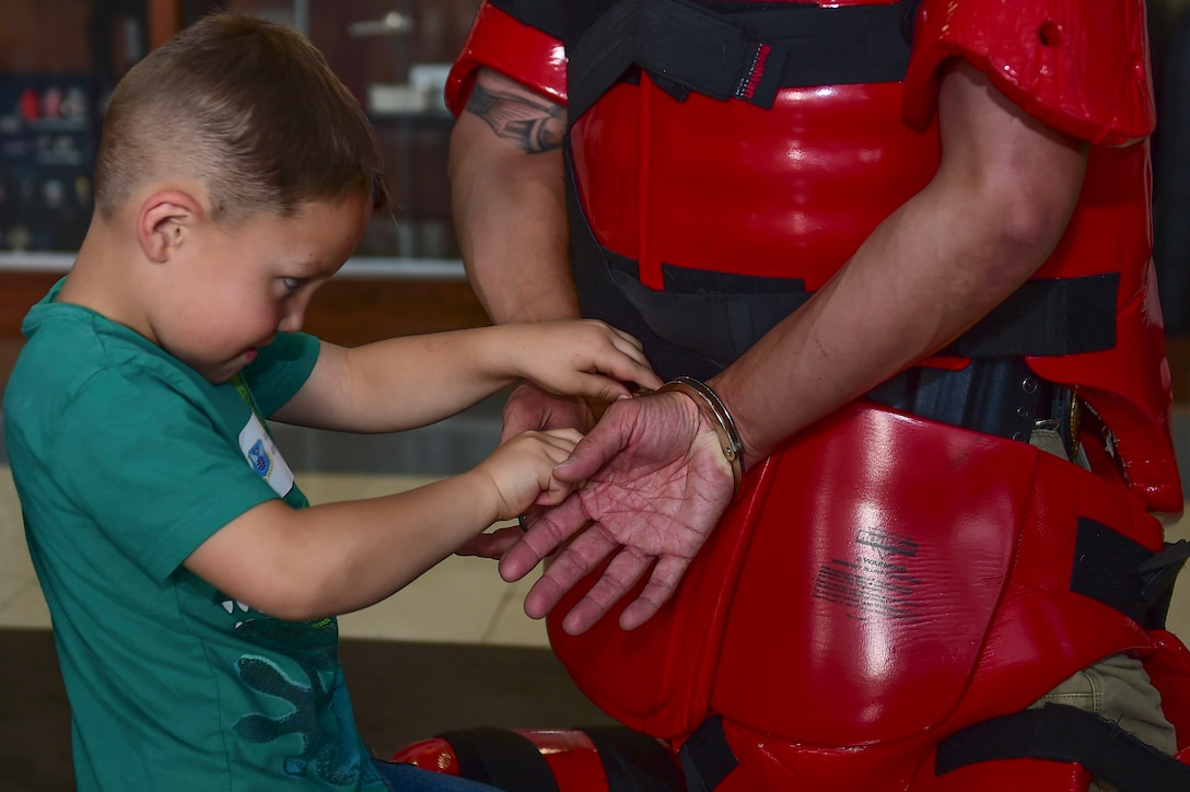 """Kai, a Buckley Youth, practices using handcuffs on Special Agent Jason, 12th Field Investigations Squadron, on """"Bring Our Daughters and Sons to Work Day"""", April 27, 2017, on Buckley Air Force Base, Colo. The children spent the day learning investigation skills, including forensics and arresting techniques. (U.S. Air Force photo by Airman Jacob Deatherage/Released)"""