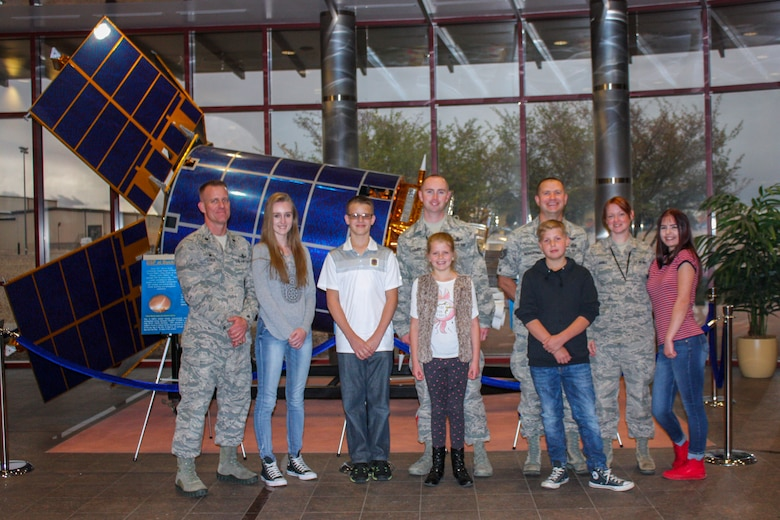Team Buckley space operators and their families pose in front of a satellite in the Mission Control Center April 27, 2017, on Buckley Air Force Base, Colo. The children received a tour of their parent's work centers and one of the radomes. (Courtesy photo)