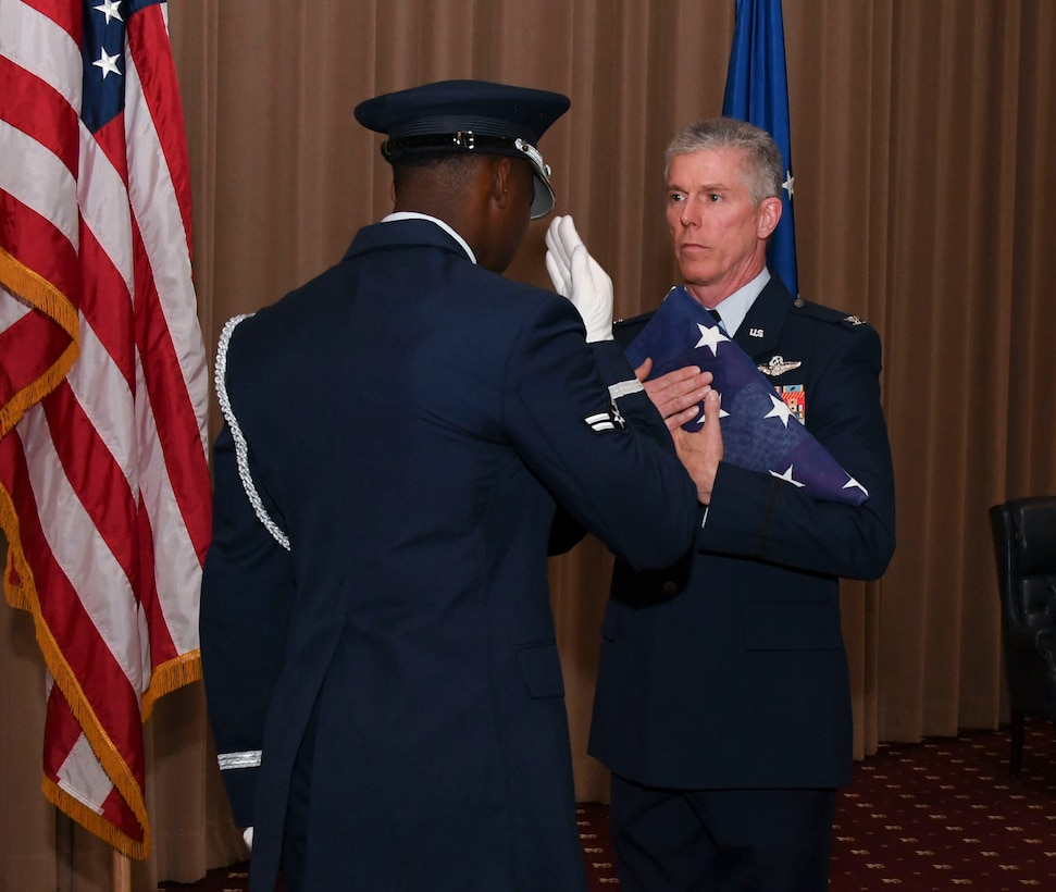 A Barksdale Honor Guardsman presents Col. James L. Morriss III, the 307th Bomb Wing vice commander, with a folded U.S. flag at Barksdale Air Force Base, La., April 29, 2017.  Morriss retired from the Air Force after serving 31 years in the military. (U.S. Air Force photo by Staff Sgt. Callie Ware/Released)