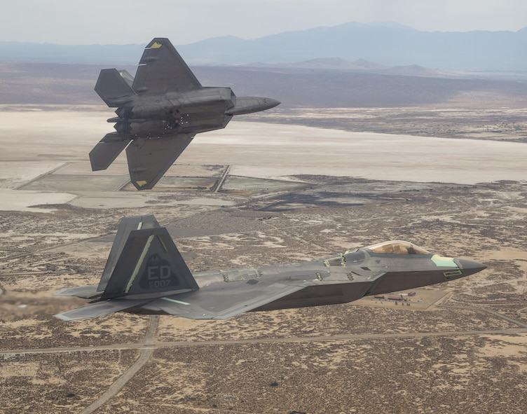 Two F-22 Raptors from the 411th Flight Test Squadron fly above the California High Desert in this photo.  Developmental tests of air-to-air missiles against an aerial target were completed April 18 at the Utah Test and Training Range as part of a major capability upgrade. (Courtesy photo by Chad Bellay/Lockheed Martin)