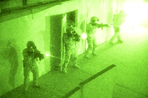 Navy SEALs clear a room during a no-light live-fire drill near San Diego, Dec. 4, 2015. Naval Special Warfare reservists from a combat service support unit conducted a field training exercise based on principles from the expeditionary warfare community. Navy photo by Petty Officer 1st Class Daniel Stevenson