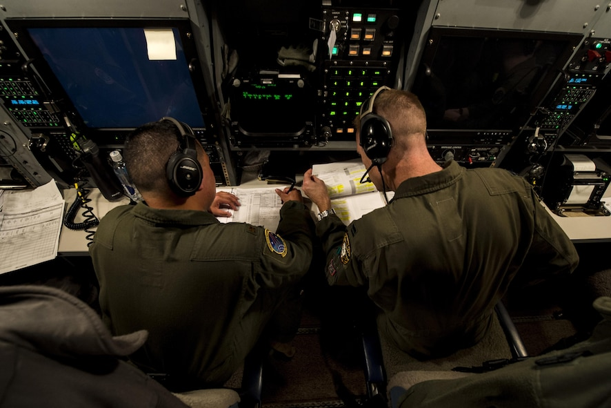 U.S. Air Force Maj. Izzy Remo, left, a test conductor-airborne, and U.S. Air Force Capt. Greg Carter, right, a deputy missile combat crew commander-airborne, both from the 625th Strategic Operations Squadron, go over missile launch procedures during Glory Flight 220 above the Pacific Ocean, April 26, 2017. Glory Trip is an operational test launch which continues a long history of launches from Vandenberg Air Force Base, Calif., used to verify, validate and improve the capability of the nation's ICBM force. (Photo edited for security) (U.S. Air Force photo by Airman 1st Class Keifer Bowes)
