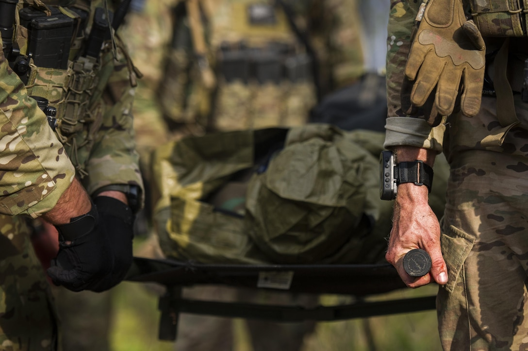 Combat aviation advisor students with the 6th Special Operations Squadron carry a litter through the woods during Operation Raven Claw at Duke Field, Fla., April 27, 2017. Students came under simulated fire from hostile forces during a checkpoint and had to navigate through the woods to a safe location while carrying a casualty weighing approximately 210 pounds. (U.S. Air Force photo by Airman 1st Class Joseph Pick)