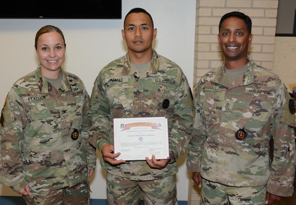 Staff Sgt. Nissan N. Armas (center) is congratulated by Col. Tayna Peacock (left), Vice Provost of Academic Affairs, Directorate of Training and Academic Affairs, U.S. Army Medical Department Center & School, and Sgt. Maj. Christopher R. Marshall (right), Sergeant Major, Directorate of Training and Academic Affairs, AMEDDC&S.