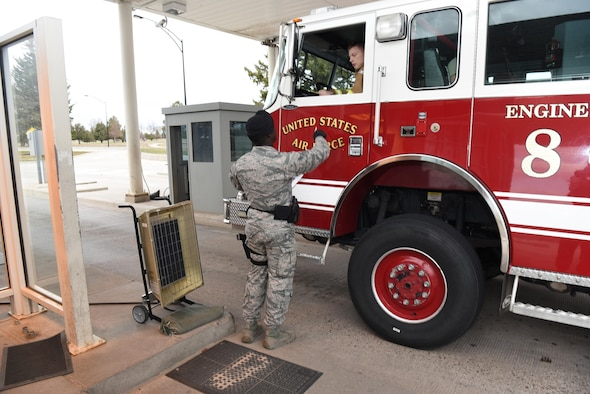 Airman 1st Class Zarquis Butler, 90th Security Forces Squadron installation entry controller, hands a firefighter back his ID card at F.E. Warren Air Force Base, Wyo., May 1, 2017. The gate guards are responsible for the safety of the installation and it's personnel. (U.S. Air Force photo by Airman 1st Class Breanna Carter)