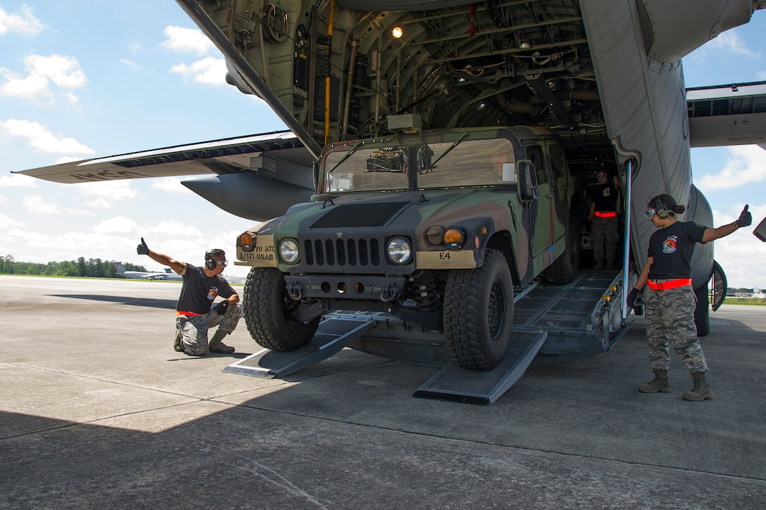 """Reserve Citizen Airmen Tech. Sgt. Eric Ignacio, left, of Honolulu, and Staff Sgt. Amber Picon, of Waipahu, give a thumbs up to Tech. Sgt. Dennis Dedicatiria, of Ewa Beach, while offloading a Humvee from the back of a C-130 Hercules aircraft during the Port Dawg Challenge at Dobbins Air Reserve Base, Ga., April 25, 2017.  The 48th Aerial Port Squadron was one of 23 teams competing in the 4th biennial Air Force Reserve Command's Port Dawg Challenge, which was designed to test and maintain the camaraderie of aerial port Airmen while promoting professionalism, leadership, training and communication between """"Port Dawgs."""" The 48th APS is located on Joint Base Pearl Harbor-Hickam, Hawaii, and a component of the Air Force Reserve, providing expertise in all areas of air terminal operations to include aircraft loading, cargo processing and inspecting, passenger services, aircraft fleet services and aerial port command and control. (U.S. Air Force photo by Master Sgt. Theanne K. Herrmann)"""