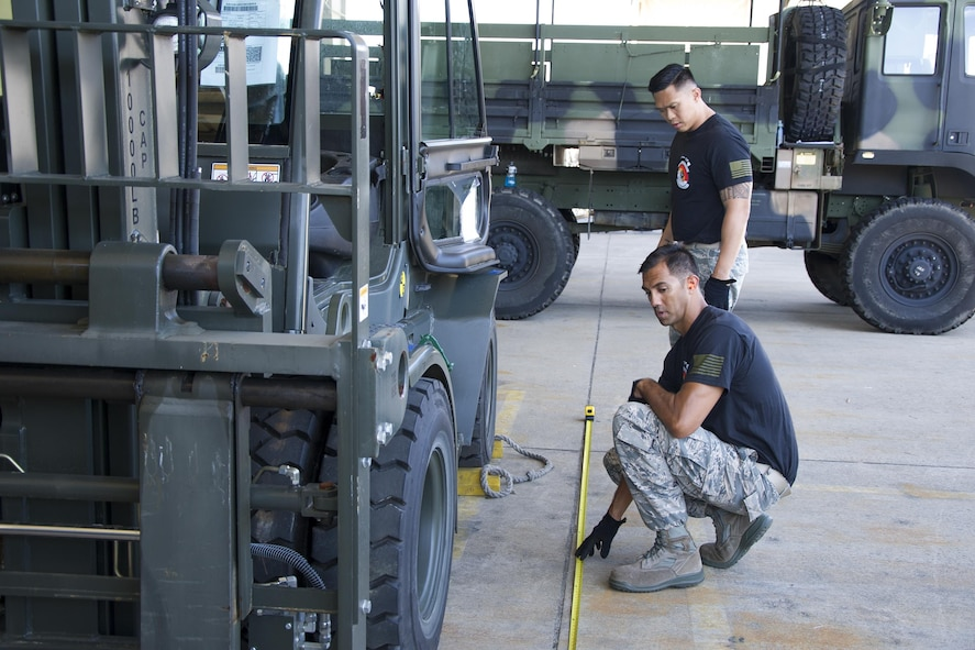 """Reserve Citizen Airmen Master Sgt. Alfred Van Gieson and Tech. Sgt. Dennis Dedicatiria, both with the 48th Aerial Port Squadron , measure the length of a 10K forklift during the joint inspection cargo load event while competing at the Port Dawg Challenge at Dobbins Air Reserve Base, Ga., April 25, 2017.  The 48th APS was one of 23 teams competing in the 4th biennial Air Force Reserve Command's Port Dawg Challenge, which was designed to test and maintain the camaraderie of aerial port Airmen while promoting professionalism, leadership, training and communication between """"Port Dawgs."""" The 48th APS, located on Joint Base Pearl Harbor-Hickam, Hawaii, is a component of the Air Force Reserve, providing expertise in all areas of air terminal operations to include aircraft loading, cargo processing and inspecting, passenger services, aircraft fleet services and aerial port command and control. (U.S. Air Force photo by Master Sgt. Theanne K. Herrmann)"""