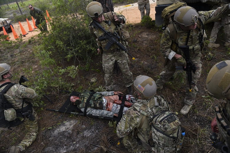 Combat aviation advisor students with the 6th Special Operations Squadron tend to a wounded casualty during Operation Raven Claw at Duke Field, Fla., April 27, 2017. Students came under simulated fire from hostile forces during a checkpoint and had to navigate through the woods to a safe location while carrying a casualty weighing approximately 210 pounds. (U.S. Air Force photo by Airman 1st Class Joseph Pick)