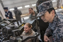 Koku-Jieitai Master Sgt. Hiroshi Osawa, right, a 2nd Air Wing Base Air Defense M-61 20 mm Vulcan cannon operator, explains the weapon's capabilities to U.S. Air Force Tech. Sgt. Jessica Nienheuser, left, the 35th Medical Support Squadron patient administration section chief, during a 10-day U.S.-Japan Bilateral Career Training, at Chitose Air Base, Japan, April 12, 2017. Nienheuser got to sit in the operator's seat while the weapon system was operational, not armed, and move the turret around while Osawa explained its operation. Koku-Jieitai is the traditional term for Japan Air Self Defense Force used by the Japanese. (U.S. Air Force photo by Tech. Sgt. Benjamin W. Stratton)