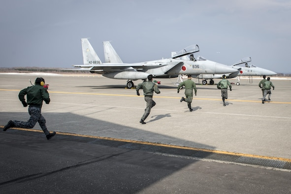 Koku-Jieitai pilots race to two Mitsubishi F-15J Eagles during a scramble demonstration as part of a 10-day U.S.-Japan Bilateral Career Training at Chitose Air Base, Japan, April 14, 2017. The scramble showcased the 2nd Air Wing's response capability to outside threats as the installation responds to incursions into Japanese airspace every week. The F-15Js offer the Koku-Jieitai a twin-engine, all-weather air superiority fighter based on the U.S. Air Force's McDonnell Douglas F-15 Eagle. Koku-Jieitai is the traditional term for Japan Air Self Defense Force used by the Japanese military. (U.S. Air Force photo by Tech. Sgt. Benjamin W. Stratton)