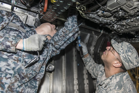 """Koku-Jieitai Tech. Sgt. Takuro Inazawa, left, a 2nd Air Wing Field Maintenance Squadron engine technician, and U.S. Air Force Tech. Sgt. Radell Mitchell, right, a 35th Maintenance Group quality assurance inspector, work side-by-side installing borescope plugs during a 10-day U.S.-Japan Bilateral Career Training at Chitose Air Base, Japan, April 18, 2017. The borescope plugs allow maintenance Airmen to inspect the internal workings of engine components. Mitchell said Inazawa taught him how Koku-Jieitai maintainers inspect their F-15J Eagles before and after take-off specifically stating just how clean and tidy they keep their jets. """"I've never seen a jet so clean and grease free before; it's obvious they have a lot of pride in the work they do for their country,"""" he said. Mitchell, along with nine other U.S. Airmen visited Chitose from Misawa Air Base, Japan. Koku-Jieitai is the traditional term for Japan Air Self Defense Force used by the Japanese. (U.S. Air Force photo by Tech. Sgt. Benjamin W. Stratton)"""