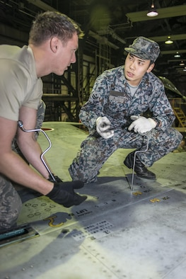 U.S. Air Force Staff Sgt. Jarrod Clark, left, a 35th Aircraft Maintenance Squadron crew chief, listens as his counterpart, Koku-Jieitai Airman 1st Class Koudai Okuguchi, right, a 2nd Air Wing Field Maintenance Squadron crew chief, explains how Koku-Jieitai maintainers care for their F-15J Eagles during a 10-day U.S.-Japan Bilateral Career Training at Chitose Air Base, Japan, April 18, 2017. Okuguchi and Clark worked together to remove a panel from the aircraft to conduct repairs before sending the jet back to the flight line for operational orders. Koku-Jieitai is the traditional term for Japan Air Self Defense Force used by the Japanese. (U.S. Air Force photo by Tech. Sgt. Benjamin W. Stratton)