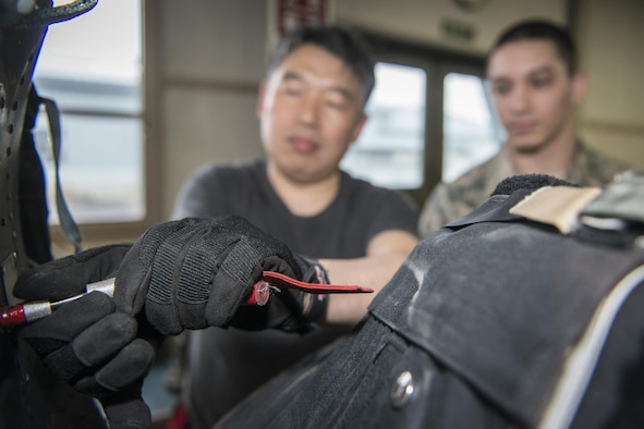 Koku-Jieitai Master Sgt. Shinichi Kishimoto, left, a 2nd Air Wing Aircrew Flight Equipment member, installs a parachute into an F-15J Eagle seat as U.S. Air Force Staff Sgt. James Berg, right, a 35th Operations Support Squadron aircrew flight equipment craftsman, observes during a 10-day U.S.-Japan Bilateral Career Training at Chitose Air Base, Japan, April 18, 2017. Working side-by-side with their Japanese counterparts, U.S. Airmen learned how the Koku-Jieitai executes their mission. Berg traveled from Misawa Air Base, Japan, with nine other U.S. Airmen for the bilateral exchange event. Koku-Jieitai is the traditional term for Japan Air Self Defense Force used by the Japanese. (U.S. Air Force photo by Tech. Sgt. Benjamin W. Stratton)