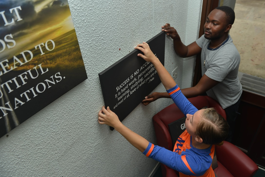 U.S. Air Force Airman Halley Mosley (left), 39th Medical Operations Squadron clinical services administrative technician, and Senior Airman Ornan Ihwagi, 39th Maintenance Squadron aerospace ground equipment journeyman, hang a canvas on the wall in the Titans' Refuge Ministry Center, May 4, 2017, at Incirlik Air Base, Turkey. The Titans' Refuge, an Incirlik chaplain corps project, is a facility for individuals to unwind, and make connections with one another. (U.S. Air Force photo by Senior Airman John Nieves Camacho)