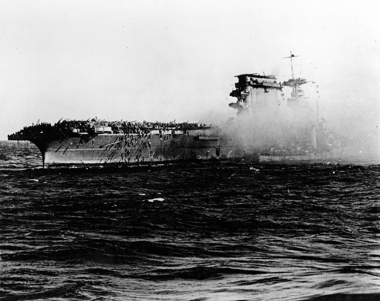 A destroyer pulls alongside the aircraft carrier USS Lexington as the carrier is abandoned during the afternoon of May 8, 1942. Note crewmen sliding down lines on Lexington's starboard quarter. Navy photo