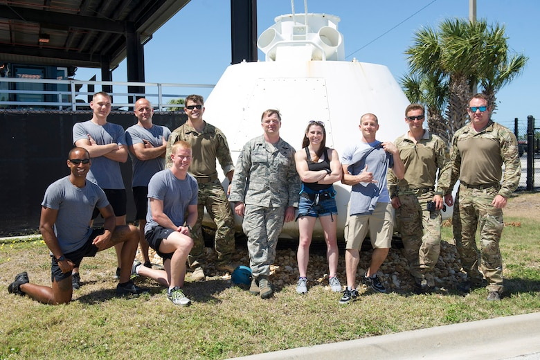 Members of the 308th Rescue Squadron pose with American Ninja Warrior stars Barclay Stockett, center, and Brent Steffensen, third from right, April 21, 2017 after they toured the unit at Patrick Air Force Base, Florida. The television stars visited as part of an Alpha Warrior Military Tour in which they visited with fans the first day and hosted a Ninja Warrior style competition the following day at the base. (U.S. Air Force photo/Phillip Sunkel)