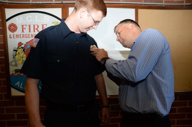 Jonathan Kirkman (left) joins Marine Corps Logistics Base Albany's firefighters' team in a ceremony, here, May 3. Jonathan's father, Phillip Kirkman, director, Retail Integration Division, Marine Corps Logistics Command, pinned on his son's badge during the event. According to Philip Partin, fire chief, Jonathan is the first entry-level trainee to graduate from the Department of Defense Fire Academy at Goodfellow Air Force Base, San Angelo, Texas, in the history of the base.