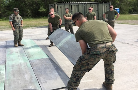 On April 19, 2017 Gunnery Sergeant Whitson, a Marine instructor with Combat Engineer Instruction Company (CEIC); supervises Combat Engineer Officer course 4-17 (CEO 4-17) students installing a 12 foot AM-2 Mat. CEO students learn how to install tactical landing surfaces called AM-2 Matting. Pictured from left to right: Gunnery Sergeant Timothy Whitson, Second Lieutenants Andrew Shrader, Camden Smith, Jonathan Lapadula, Daniel Asheim, Joshua Keeven, and Ryan Christmas.