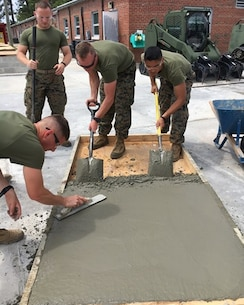 On May 1, 2017 students attached to Combat Engineer Officer course 4-17 (CEO 4-17) use a concrete float and shovels to smooth the concrete added to a form. CEO students learn how to calculate concrete production during this course at Marine Corps Engineer School in Camp Lejeune, N.C. Pictured from left to right: Second Lieutenants Camden Smith, Daniel Asheim, Andrew Shrader, and Jonathan Lapadula.
