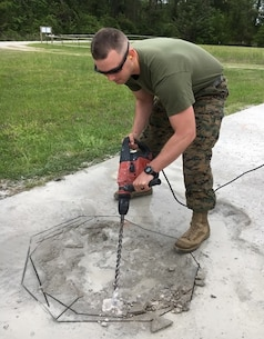 On April 19, 2017 Second Lieutenant Ryan Christmas, a Marine attached to Combat Engineer Officer course 4-17 (CEO 4-17); removes the uneven corners of a spall with a concrete drill.  CEO students learn how to repair spalls and crater damage on an airfield utilizing tools from the Airfield Damage Repair kit at Marine Corps Engineer School aboard Courthouse Bay, Camp Lejeune, N.C.
