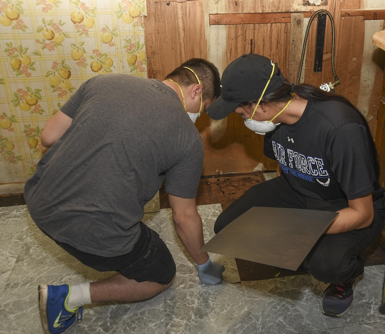 Senior Airman Johnneil Rojas, left, and Senior Airman Lalynn Antell, right, 11th Civil Engineer Squadron engineering assistants, lay linoleum tiles at a house in College Park, Md., April 29, 2017 More than 20 Joint Base Andrews 11th CES Airmen partook in the 2017 Christmas in April Prince George's County, an annual volunteer program that repairs the homes of low-income or physically challenged senior citizens in one day. The renovations included electrical, plumbing and structural repairs. (U.S. Air Force photo by Airman 1st Class Rustie Kramer)