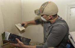 Senior Airman Merrit Metzler, 11th Civil Engineer Squadron structures journeyman, repairs a hole in a wall at a house in College Park, Md., April 29, 2017. More than 20 Joint Base Andrews 11th CES Airmen partook in the 2017 Christmas in April Prince George's County, an annual volunteer program that repairs the homes of low-income or physically challenged senior citizens in one day. The renovations included electrical, plumbing and structural repairs. (U.S. Air Force photo by Airman 1st Class Rustie Kramer)