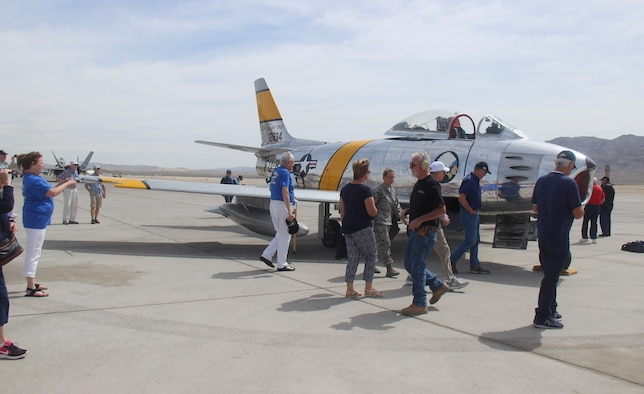 Members of the F-86 Sabre Association view an F-86 Sabre during the group's last reunion on the flightline at Nellis Air Force Base, Nev., April 24, 2017. The F-86 Sabre was originally designed as a high-altitude fighter, making it highly valued during the Korean War. (U.S. Air Force photo by Susan Garcia/Released)
