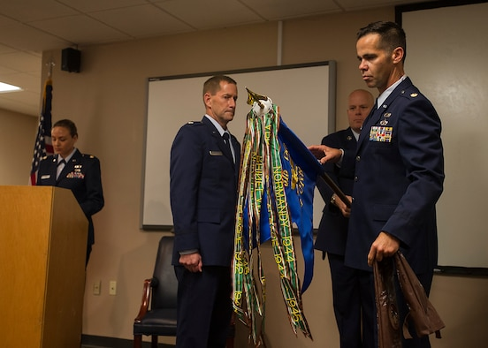 (from left) Lt. Col. John Robinson, 315th Operations Group commander, watches Maj. Hamilton Underwood, the units commander, unravel the 4th CCTS colors during a unit reactivation and assumption of command ceremony at Joint Base Charleston, S.C., May 5. The 4th CTCS, which was formally assigned to March Air Reserve Base in Riverside, Calif., deactivated in July 2015, but was reactivated and relocated to the 315 AW due to mission need. (U.S.Air Force Photo by Michael Dukes)