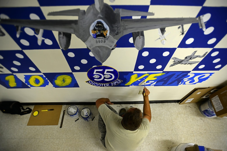 U.S. Air Force Tech. Sgt. Brian Barnes, 20 Aircraft Maintenance Squadron, 55th Aircraft Maintenance Unit (AMU) tactical aircraft maintainer, applies the first coat of paint to the '100 Years' portion of a mural at the 55th AMU building at Shaw Air Force Base, S.C., April 24, 2017. The mural was designed to showcase the history and achievements of the 55th Fighter Squadron across 100 years. (U.S. Air Force photo by Senior Airman Kelsey Tucker)