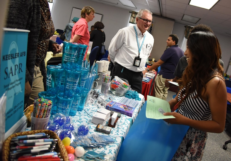 Barry Newman, sexual assault victim advocate, provides information about the sexual assault prevention and response program to Alana Trujillo, spouse of Staff Sgt. Javier Trujillo, 334th Training Squadron instructor, during Pamper Me Day at the Sablich Center May 4, 2017, on Keesler Air Force Base, Miss. Keesler's Airman and Family Readiness Center has hosted the event for the past 13 years, offering spouses free manicures, make-up styling tips and information and business booths. (U.S. Air Force photo by Kemberly Groue)