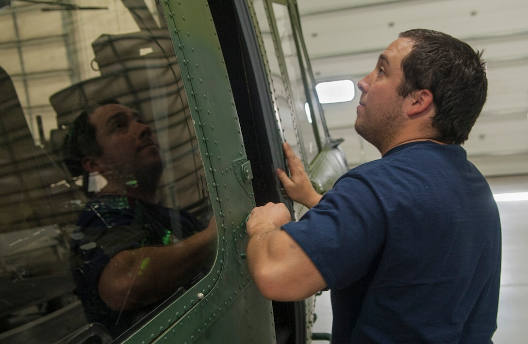 Thomas Martinez, 54th Helicopter Squadron aircraft mechanic, closes a helicopter cabin door at Minot Air Force Base, N.D., May 2, 2017. Squadron members also engage in emergency search and rescue mission training. (U.S. Air Force photo/Airman 1st Class Jonathan McElderry)