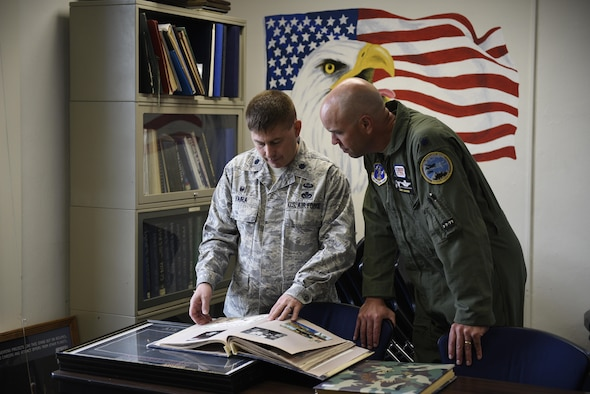 Lt. Col. Rusty Vaira, 219th Rapid Engineer Deployable Heavy Operational Repair Squadron Engineer, or RED HORSE Squadron commander, and Lt. Col Larry Gardner, 120th Airlift Wing Operations Support Squadron commander, flip through albums at the Air Force Reserves Officers' Training Corps detachment 450 Montana State University, Bozeman April 24, 2017 in the ROTC classroom. Vaira, a graduate of Det. 450 was asked to speak to the cadets on his career path and had a chance to reminice about his beginnings in the detachment. (U.S. Air National Guard photo by Staff Sgt. Lindsey Soulsby)