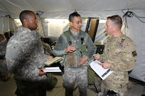 "Capt. Alphonso Williams, S1 of the 457th Transportation Battalion, and Capt. Bach Dang, battalion executive officer, discuss the operations order production process with Observer Controller/Trainer Capt. Scott Dyer of 1st Brigade, Great Lakes Training Division, 75th Training Command, during a break from instruction on the Military Decision Making Process. During the ""warm start"" of WAREX 86-17-02 at Ft. McCoy, Wisconsin, participating units are developing the operations order to be used in the exercise using the MDMP, while receiving instruction on the process."