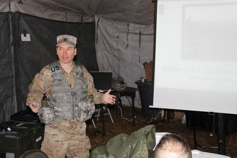 Capt. Robert Reynolds, an observer controller/trainer in 1st Brigade, Great Lakes Training Division, 75th Training Brigade, explains the course of action development step of the Military Decision Making Process to members of the 419th Combat Service Support Battalion, headquartered in Tustin, California.