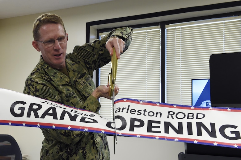 U.S. Navy Capt. Robert Hudson, Joint Base Charleston deputy commander, cuts the ribbon to mark the beginning of the Reduced Oxygen Breathing Device operations May 2, 2017. Because the device is available locally, 1,200 Airmen can receive onset hypoxia training annually without the added requirement of traveling to an installation with an altitude chamber. ROBD training allows aviators and aircrew to experience hypoxia without the threat of decompression sickness associated with the altitude chamber.