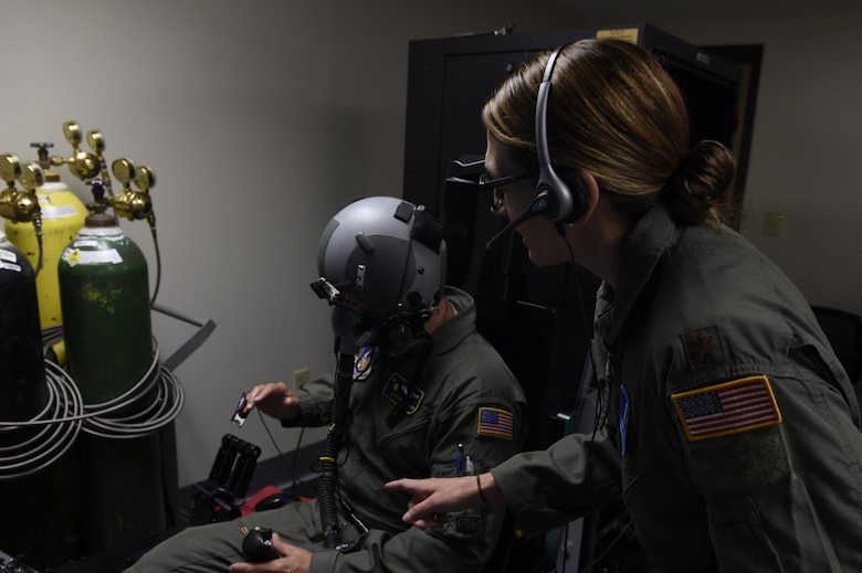 Maj. Kasie Gaona, Air Force Reservist, prepares a student for Aerospace Physiology refresher training using the Reduced Oxygen Breathing Device and Hypoxia Familiarization Trainer May 3. By using the device, Airmen receive their five-year required physiology training in a realistic simulation, locally and without the risks associated with the hypobaric chamber.