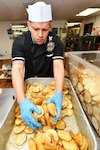 Navy culinary specialist Petty Officer 2nd Class Roel Caballero, assigned to Naval Base Kitsap-Bangor's Trident Inn Galley, in Silverdale, Wash., seasons and mixes sliced potatoes for lunch, May 2, 2017. Navy photo by Petty Officer 3rd Class Charles D. Gaddis IV