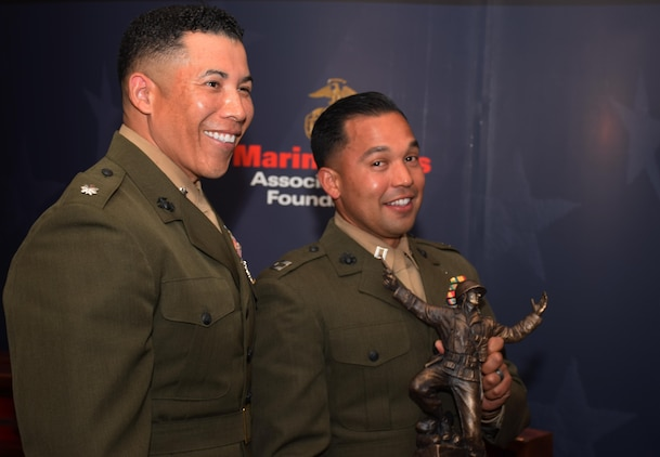 """Lt. Col. Esteban Beamon (left), the commander of Detachment 2, 4th Civil Affairs Group, Marine Forces Reserve, stands by Capt. Ismael Lopez (right), the civil military operations planner for Special Purpose Marine Air-Ground Task Force-Southern Command 17, who holds up the 2016 Colonel Justice Marion """"Jumping Joe"""" Chambers Award at the Marine Corps Association and Foundation Ground Awards Dinner in Arlington, Va., May 4, 2017. The award recognized Lopez as the Marine Corps Reserve company grade officer of the year for demonstrating outstanding leadership qualities during the transition of Detachment 4, 4th Tank Battalion to 4th Civil Affairs Group. (Courtesy Photo by Marine Corps Association and Foundation/Released)"""