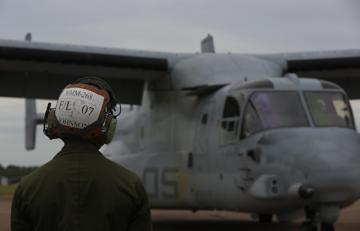 """A Marine with Marine Tiltrotor Squadron (VMM) 268 guides an MV-22B Osprey into position after the aircraft landed at Royal Australian Air Force Base Darwin, Australia, April 28, 2017. Four MV-22B Ospreys arrived to begin a deployment to Marine Rotational Force-Darwin 17.2. VMM-268, also known as the """"Red Dragons,"""" are the first to make a trans-Pacific flight with the MV-22B Osprey. (U.S. Marine Corps photo by Lance Cpl. Damion Hatch)"""