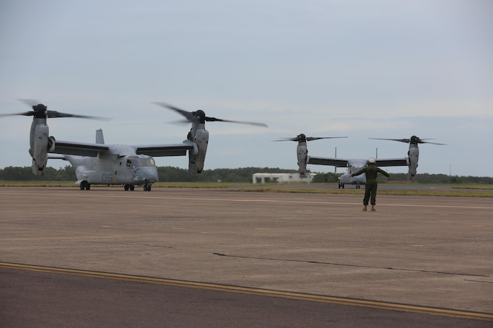 A Marine with Marine Tiltrotor Squadron (VMM) 268 guides an MV-22B Osprey into position after the aircraft landed at Royal Australian Air Force Base Darwin, Australia, April 28, 2017. Four MV-22B Ospreys arrived to begin a deployment to Marine Rotational Force-Darwin 17.2. The Ospreys flew approximately 6,000 miles across the Pacific in 21-hours of flight time. (U.S. Marine Corps photo by Lance Cpl. Damion Hatch)