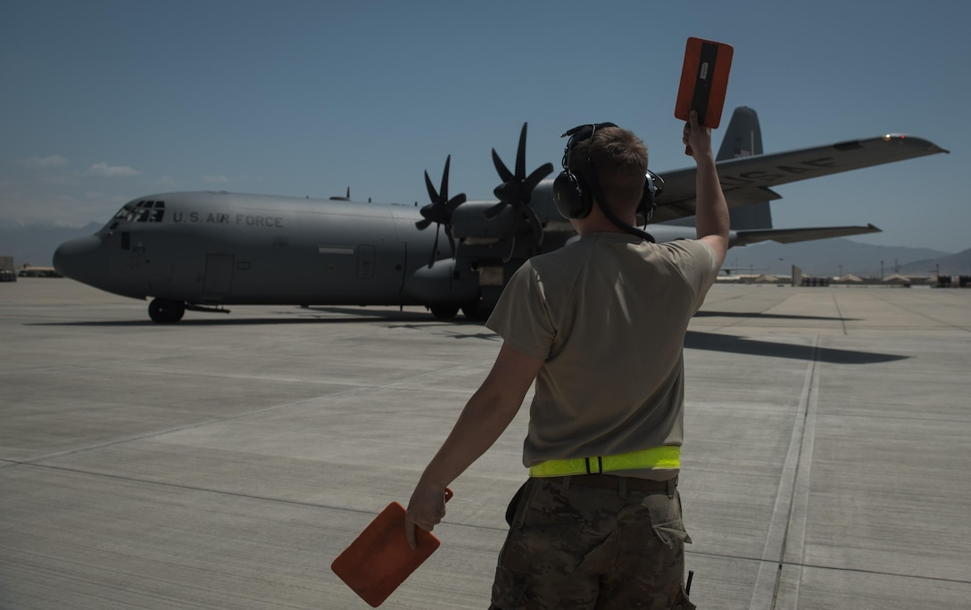 Senior Airman Phillip Vaughn, a 455th Expeditionary Aircraft Maintenance Squadron crew chief, marshals a C-130J Super Hercules at Bagram Airfield, Afghanistan, May 5, 2017. Marshalling is the use of hand signals to direct the pilot where to maneuver the aircraft and when to stop. (U.S. Air Force photo by Staff Sgt. Benjamin Gonsier)