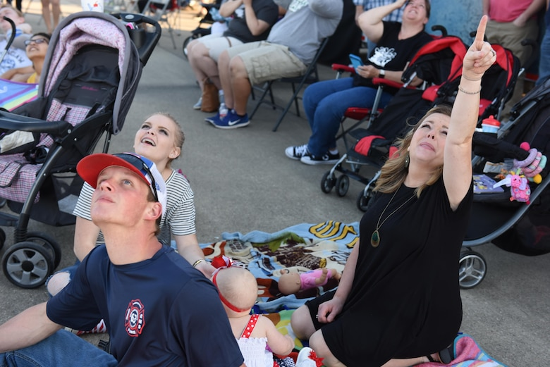 Spectators react to the Canadian Skyhawks as the parachutists jump out of a C-17 Globemaster during the 2017 Defenders of Liberty Air Show at Barksdale Air Force Base, La., May 5, 2017. The inherent flexibility of the C-17 allows it to fulfill the worldwide air mobility requirements of the U.S. through rapid strategic delivery of troops and cargo. (U.S. Air Force photo/Senior Airman Luke Hill)