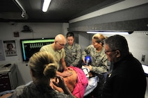 Branden Marienau, Simulation in Motion South Dakota (SIMSD) education coordinator, shared a few tips with a team of medics from the 114th Medical Group during a simulated medical emergency in the SIMSD Vehicle on Joe Foss Field May 6, 2017.  The Vehicle was visiting Jose Foss Field in order to provide realistic trauma emergency simulations to the medics from the 114th Medical Group.  (U.S. Air National Guard photo by Master Sgt. Christopher Stewart/Released)