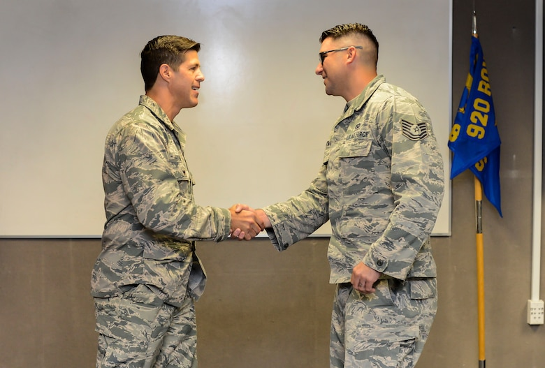 During the 920th Rescue Wing's drill training weekend May 7, 2017, Vice Wing Commander Col. P. Brett Howard presented Tech. Sgt. Shauen Hartman with the wing commander's coin at the 308th Rescue Squadron where he serves as a medical logistics technician, for his heroics. While surf fishing off the beach at Patrick Air Force Base, Florida, Hartman risked his life to save 8 others who got caught in rip currents April 14, 2017.